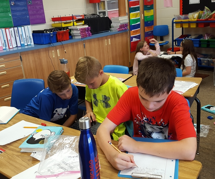 5th graders working cooperatively rewriting a chapter in Wonder from a different point of view.