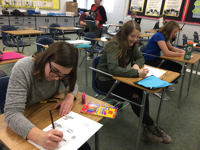 8th grade social studies students hard at work on their political cartoons.
